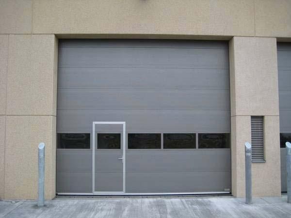 Серые секционные автоматические ворота с калиткой и стеклом