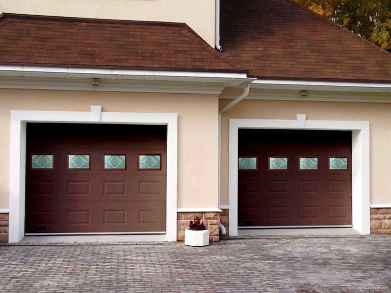 Коричневые секционные ворота в гараж частного дома со стеклом